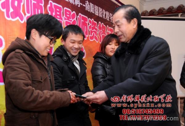 王校长为摄影班陈妍同学颁发南阳民俗摄影协会会员证